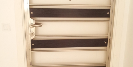 Stainless steel door grille with wood finish aluminum panels.